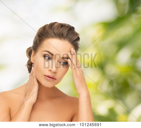 health and beauty concept - depressed woman holding hands on her neck and forehead