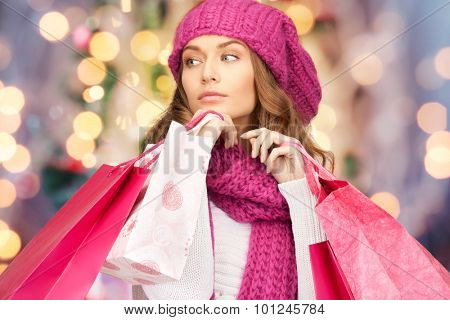 holidays, christmas, sale and people concept - young woman in winter clothes with shopping bags over lights background