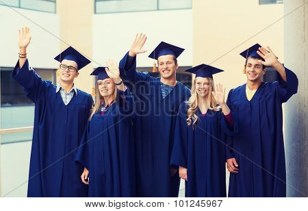 education, graduation and people concept - group of smiling students in mortarboards and gowns waving hands outdoors