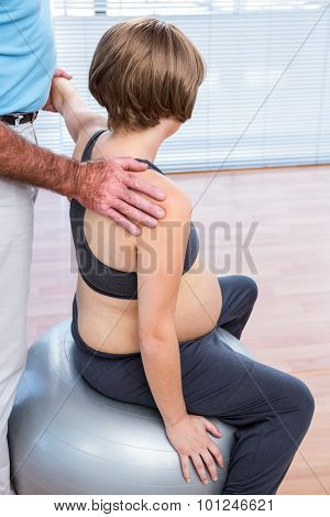Therapist giving treatment to pregnant woman sitting on exercise ball