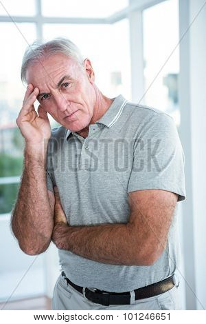 Portrait of tensed man touching his head while standing against window