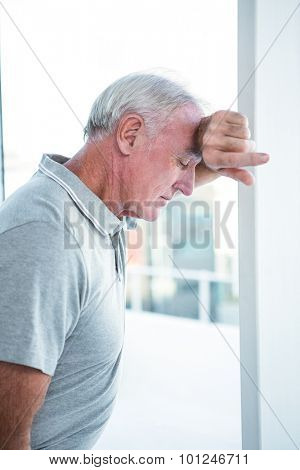 Depressed mature man leaning on wall at home