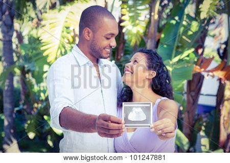 Happy man with pregnant wife holding sonogram against white background