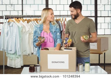 Colleagues discussing while separating products from donation box