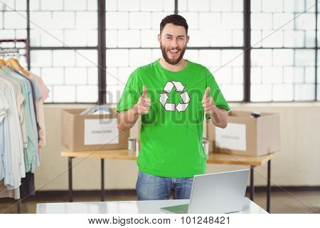 Portrait of happy man in recycling symbol tshirt showing thumbs up in office