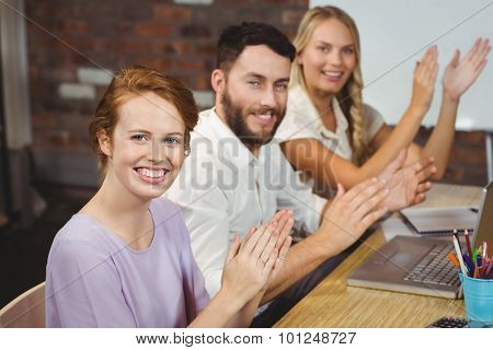 Portrait of happy colleagues clapping at meeting in creative office