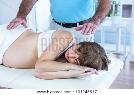 Male therapist performing reiki over pregnant woman at health club