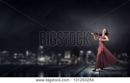 Young female violin player in long evening brown dress