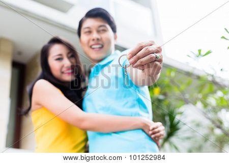 Chinese couple, woman and man, showing keys to their new home moving in