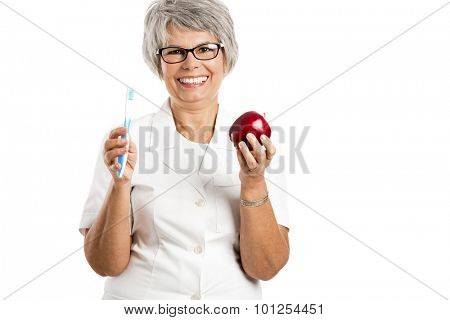 Happy old female doctor holding a apple and a toothbrush isolated on white