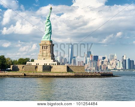 The Statue of Liberty with the New York skyline on the background on a beautiful summer day
