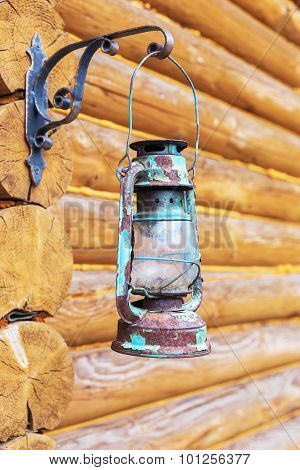 Old Retro Kerosene Lantern Hanging On The Wall Of The Log House As A Background For Creative Design.