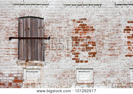 Old Window With Creative Metal Bars On The White Stone Wall