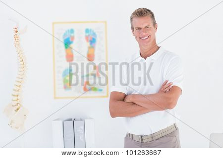 Happy doctor looking at camera with arms crossed in medical off