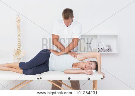 Doctor examining his patient pelvis in medical office