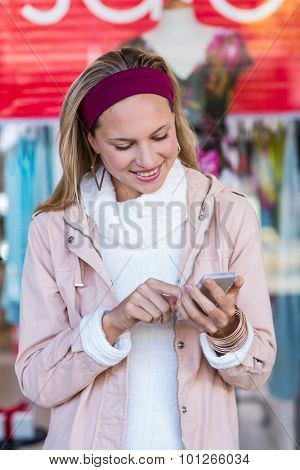 Smiling woman using smartphone in front of window at shopping mall
