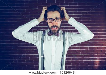 Portrait angry man with head in hands against brick wall