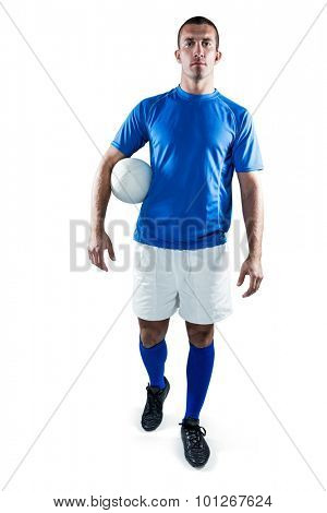 Full length portrait of rugby player looking away while holding ball aside against white background