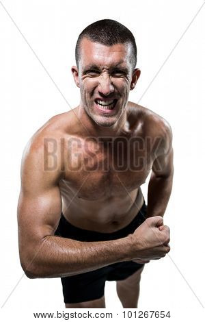 Portrait of excited shirtless athlete flexing muscles against white background
