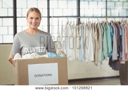 Portrait of beautiful woman volunteer holding clothes donation box