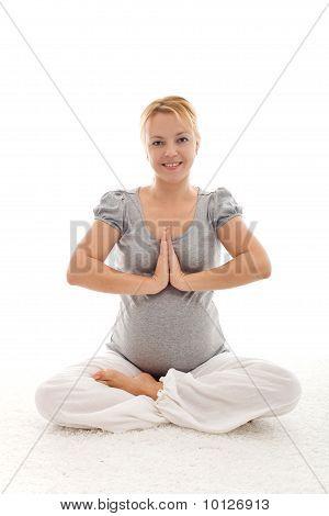 Schöne schwangere Frau, die Übungen auf dem Boden