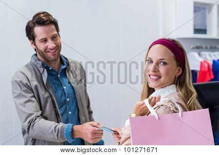 Portrait of smiling woman getting back credit card in clothing store