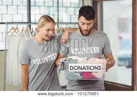 Volunteers looking at clothes in donation box at office