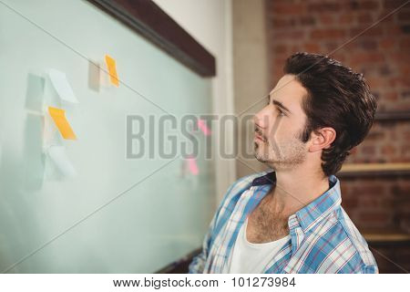 Businessman reading sticky notes on glass board in office