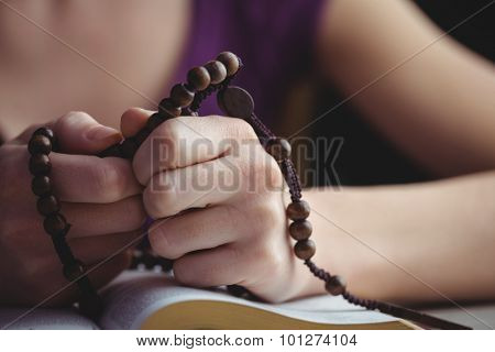 Woman praying with her bible and rosary beads in close up