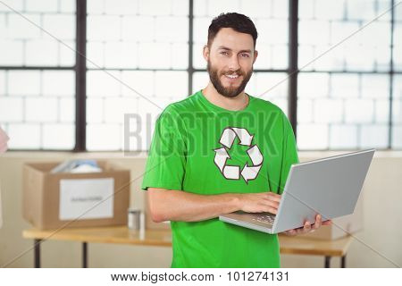 Portrait of man in recycling symbol tshirt working on laptop while standing in creative office