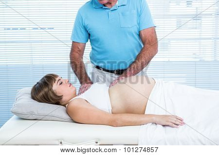 Male masseur massaging pregnant woman lying on bed at health club