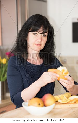 Woman In The Kitchen With An Orange