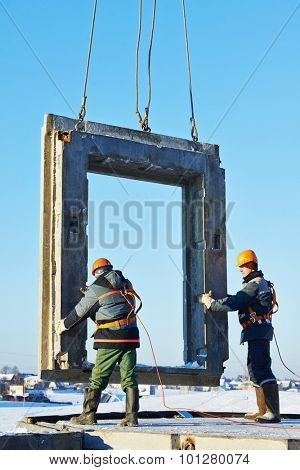 builder worker in safety protective equipment installing concrete wall panel at building construction site