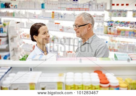 medicine, pharmaceutics, health care and people concept - happy pharmacist talking to senior man customer at drugstore