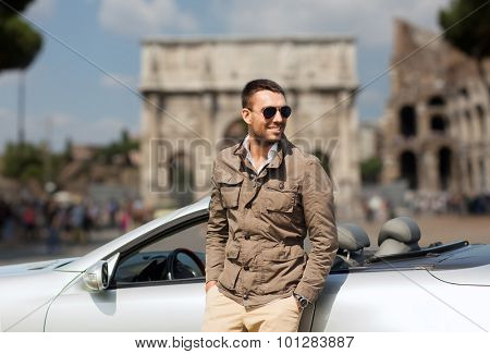 travel, tourism, road trip, transport and people concept - happy man near cabriolet car over triumphal arch in city of rome background