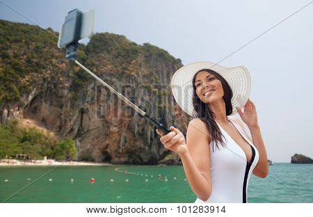travel, leisure, summer, technology and people concept - sexy young woman taking selfie with smartphone over sea and island rock at tropical beach on bali background