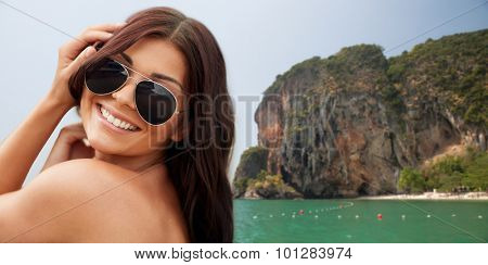 summer vacation, tourism, travel, holidays and people concept -face of smiling young woman with sunglasses over sea and island rock at tropical beach on bali background