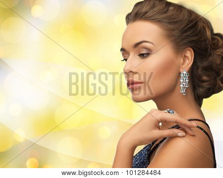 people, holidays and glamour concept - smiling woman in evening dress wearing earrings over yellow lights background