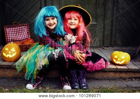 Little friendly girls in Halloween attire looking at camera