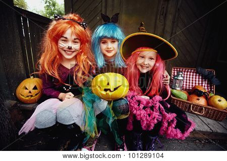 Smiling girls surrounded by Halloween symbols looking at camera