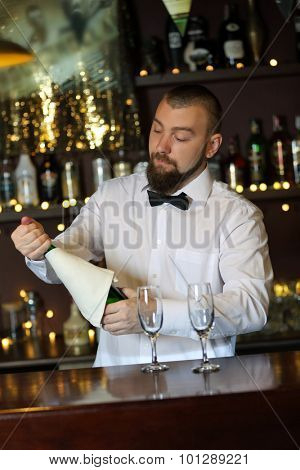 Portrait of handsome bartender with champagne bottle