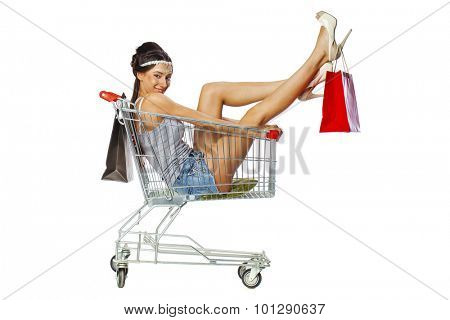 Happy young beautiful brunette woman sits in an empty shopping cart with a red bag, isolated on white background