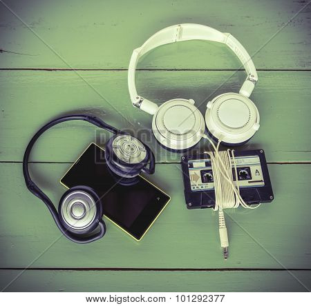 Smartphone Cassette Tape And Headphone On The Wood Board