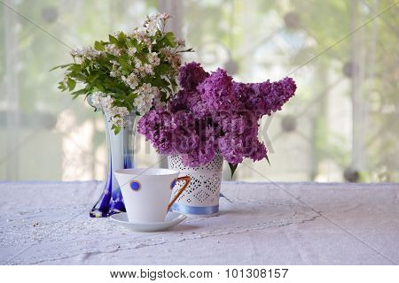 Tea In A Beautiful Cup And A Bouquet From Lilac Branches