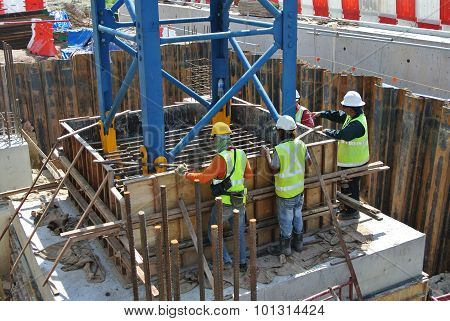 Group of construction workers fabricating pile cap formwork