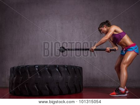 Fit girl with tire and hammer