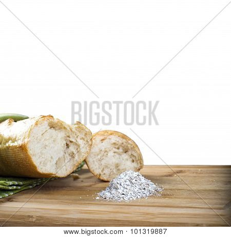 Long baguette and flour on wooden cutting board