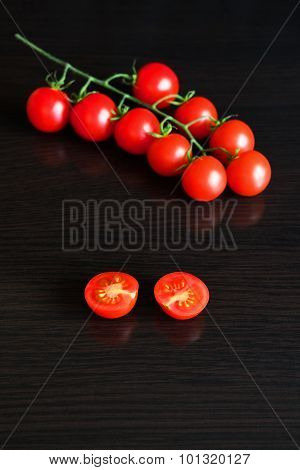 Red cherry tomato on dark wooden table