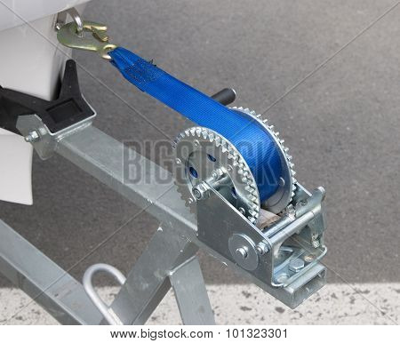 Boat trailer winch with blue rope.
