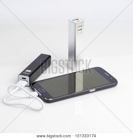 Charging a smartphone from powerbank on white table